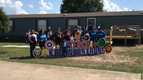 Khonner and the Motorcycle Club posing by a #KhonnerStrong yard sign.