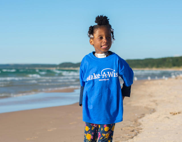 A child with dark curly hair stands on the beach next to the water. The child is wearing a royal blue Make-A-Wish t-shirt and black floral patterned leggings.