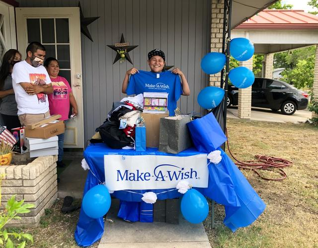 Wish Kid Victoria holding up her Make-A-Wish CSTX shirt with her shopping spree presents