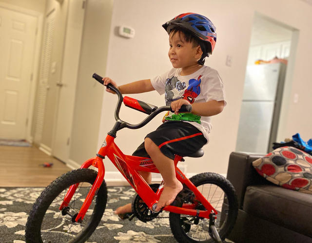 A young child with dark hair rides a red bike across a carpeted room. The child is wearing a blue and red bicycle helmet, a white Superman t-shirt, and black athletic shorts.