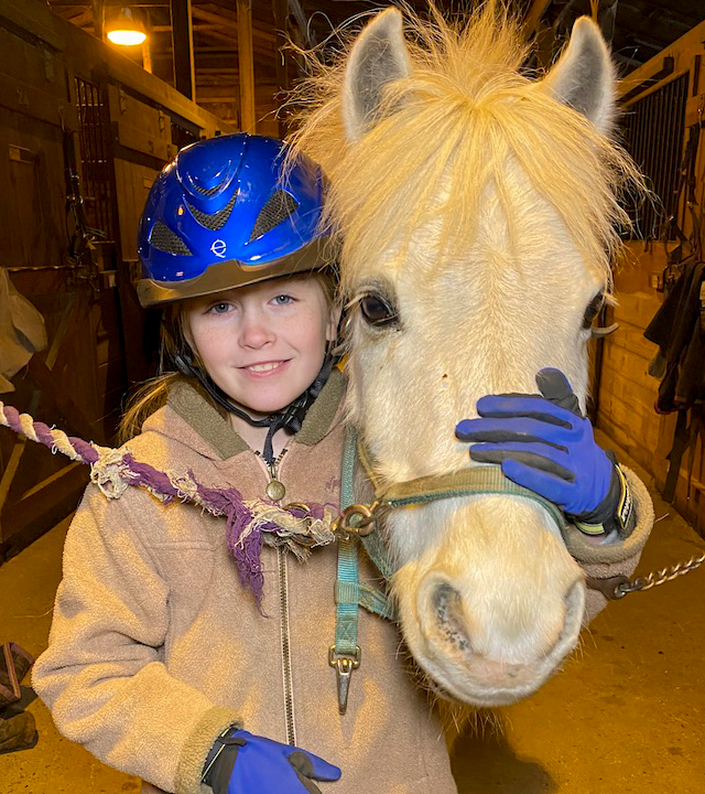 Elizabeth with her white horse, Prince Aladdin, in the barn.