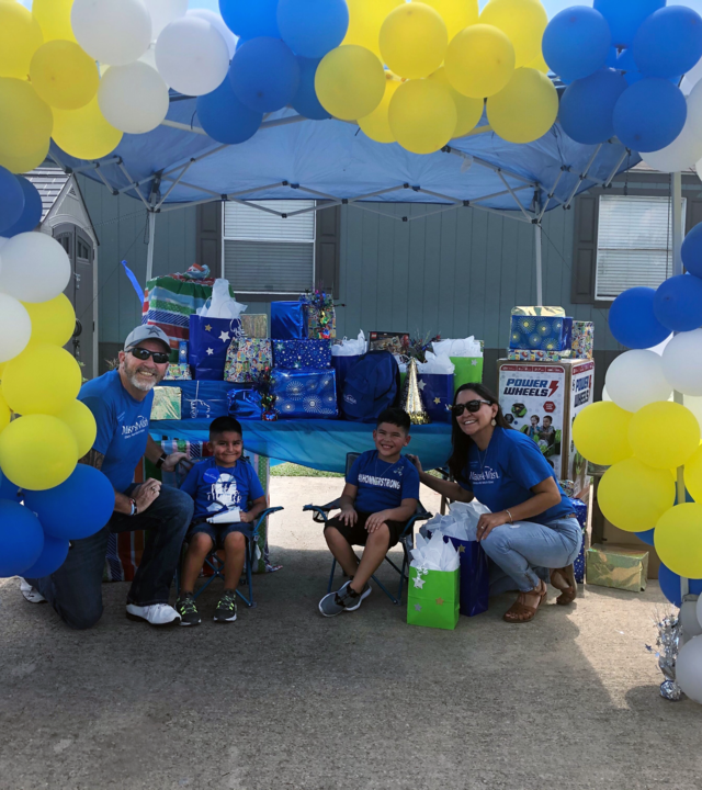 Wish Kid Khonner and brother Koda with Make-A-Wish Volunteers under a balloon arch.
