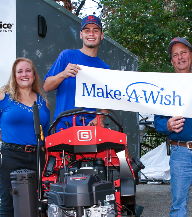 Mason with mom and company rep holding Make-A-Wish sign standing on red lawnmower.