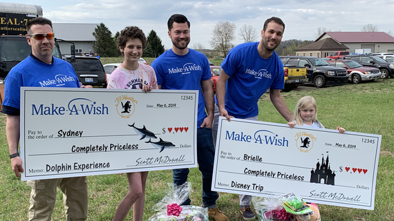 "Three adults wearing royal blue t-shirts with the Make-A-Wish Michigan logo pose for a photo with a teenager with short curly brown hair and a child with straight blond hair. Both children hold oversized checks with the Make-A-Wish and All-Weather Seal company logos, symbolizing that All-Weather Seal has adopted their wishes. The checks are made out to the children for a ""Completely Priceless"" amount, with a description of their wish on the memo line—a dolphin experience for the teenager and a Walt Disney W"