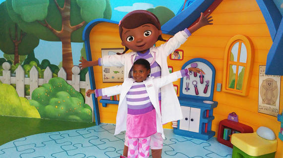 An 8-year-old child in a purple, pink, and white dress, white lab coat, and pink and purple polka dot leggings poses with Doc McStuffins in front of an orange and blue cartoon playhouse stage set.