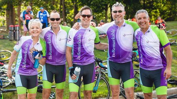 Five adults pose with their arms around each other. They are wearing matching green and purple cycling outfits with the Trinity Health logo. In the background, their bikes are laying on the grass.