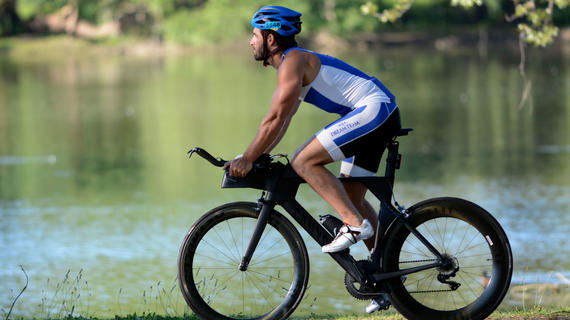 An adult wearing a blue and white cycling outfit and royal blue helmet rides a black bike along a waterside trail.
