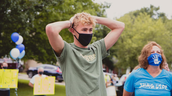Drew wearing a mask while he his surprised by volunteers with balloons and signs