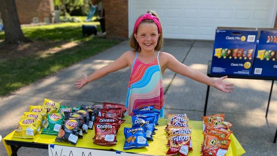 "A child in a hot pink headband and brightly colored dress stands with arms thrown out wide behind a snack stand fundraiser. In front of the child, a table covered with a bright yellow plastic tablecloth is filled with individual variety bags of potato chips. A sign taped to the front of the table reads ""WAM (Wish-A-Mile) Fundraiser"" and advertises lemonade, water, and snacks for sale."