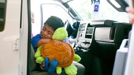 Juan hugging plush turtle during his grand welcome to Hawaii