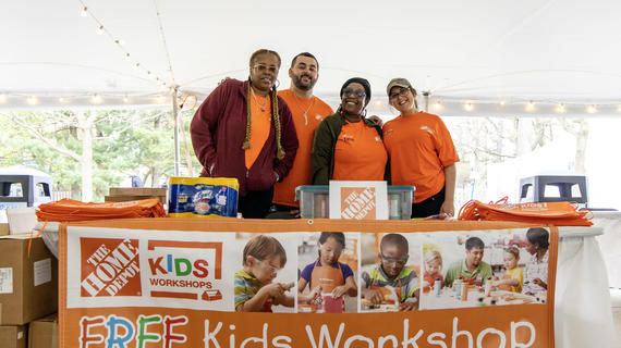 Four adults wearing matching bright orange t-shirts stand behind a table filled with orange aprons, Lysol wips, and a bin of crafting supplies. A banner on the front of the table advertises a free kids works