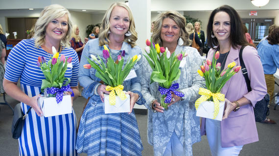 Four adults in business casual attire show off their multi-colored tulip arrangements.