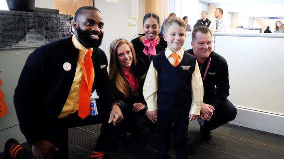 A six-year-old child with short blond hair poses for a photo with the flight crew for a wish trip. The child wears a custom matching flight attendant's uniform, complete with a pair of wings pinned to a navy blue vest. Four adults in navy suits with pale yellow shirts and orange ties or scarves kneel behind the child in the airport boarding area.