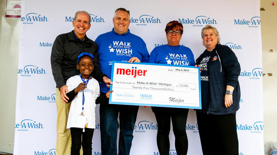 "Four adults and a wish kid pose for a photo in front of a white background patterned with royal blue Make-A-Wish Michigan logos. They are wearing royal blue or navy t-shirts that say ""Walk with me. Wish with me."" and holding an oversize check with the Meijer logo on it acknowledging the company's sponsorship of the 2019 Walk For Wishes event."
