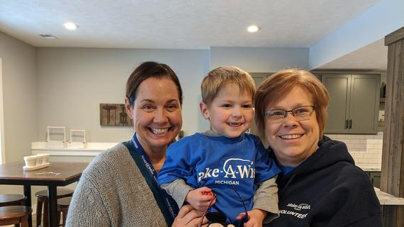 A young child with short blond hair is wearing a royal blue Make-A-wish t-shirt over a long-sleeved gray shirt and clutching a stuffed Mickey Mouse toy as two wish-granting volunteers hug him during a wish discovery meeting.