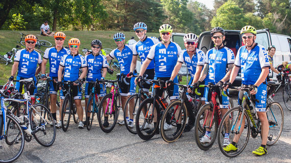 Ten members of the Eaton Wish-A-Mile cycling team pose in a line for a photo with their bikes. They are wearing matching blue and white cycling outfits with the Eaton logo on them and brightly colored helmets.