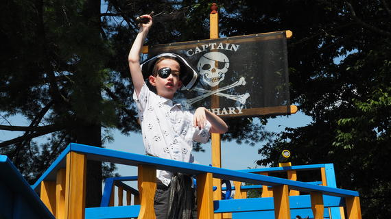Zachary plays in his pirate playhouse dressed as a pirate