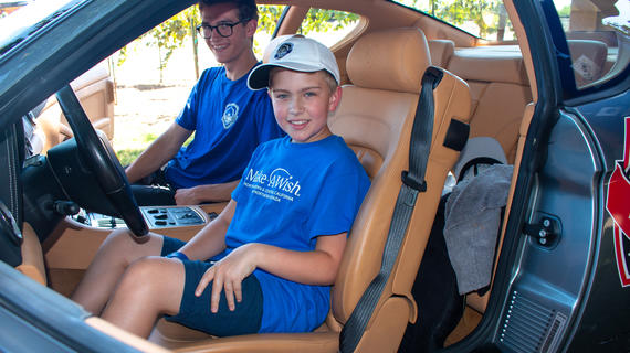 Wish kid in Make-A-Wish T-shirt in the drivers seat of a stopped car