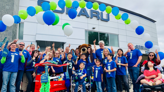Rini celebrates her wish coming true with the team at Subaru.