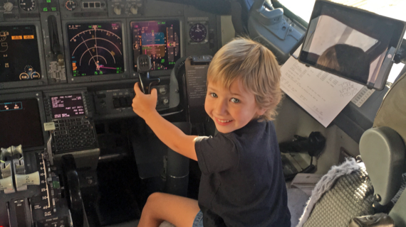 Wish Kid Avery in the cockpit of a plane behind the wheel
