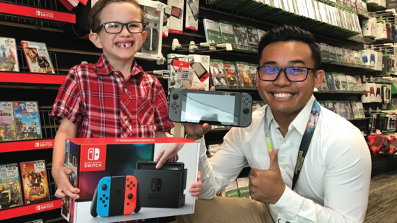 Wish Kid Landon poses with a Gamestop employee with his Nintendo Switch System