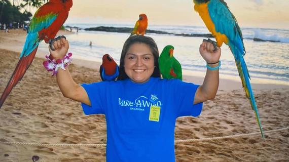 Isabelle on beach holding parrots