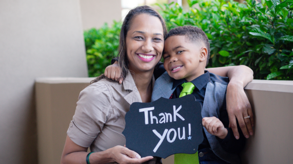Wish Mom and kid hold a 'thank you' sign