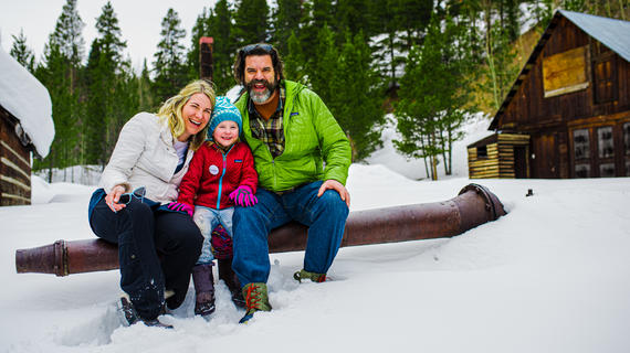 Family in the snow in front of a forest and a cabin