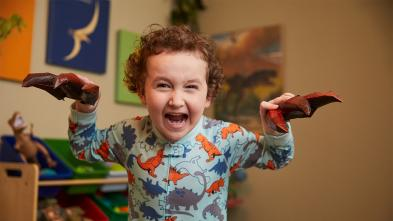 Dressed in gray pajamas covered with multi-colored dinosaurs, a 4-year-old child pretends to be a dinosaur roaring. In the background is a playroom, with a shelf full of toys and dinosaur images on the walls.