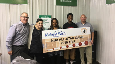 Four adults stand with a teenage wish kid in front of a wall that has many signs with inspirational sayings. The group of people holds a large countdown sign with the Make-A-Wish Michigan and All Weather Seal company logos and images of basketballs and a basketball court.