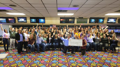 A large group of people gather together in a bowling alley for a photo. Many of them have thrown their hands in the air. In the front of the group, two adults are kneeling and holding an oversize check, made out for sixty thousand dollars to Make-A-Wish Michigan from Arby's.