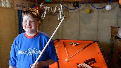 "A child with short brown hair wearing a royal blue Make-A-Wish t-shirt stands with a billiard cue in hand in front of a pool table with orange felt. Three additional cues, balls, and other billiards equipments are scattered on the table. In the background above the child's head is a silver balloon that says ""yay!"""