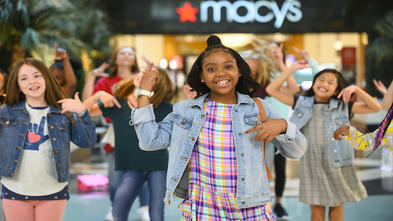 Surrounded by smiling friends, an 8-year-old child wearing a multi-colored plaid dress and light wash jean jacket dances enthusiastically.