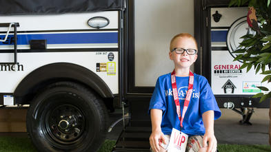 A child with short red hair and black glasses sits on the entry ramp to a camper. The child is wearing a royal blue Make-A-Wish t-shirt, tan plaid shorts, and a red lanyard with a large tag that says VIP.