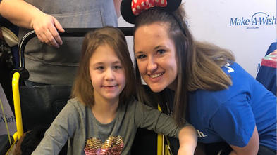 An adult with shoulder-length straight dark hair crouches next to a child sitting in a yellow wheelchair. The adult is wearing a royal blue Make-A-Wish t-shirt, jeans, and Minnie Mouse ears. The child is wearing a long-sleeved gray t-shirt with a multi-colored heart, jeans, and purple cowboy boots and clutching a large brown and white stuffed horse.