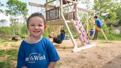 A young child in a royal blue Make-A-Wish t-shirt with brown hair pulled into a loose ponytail stands in front of a backyward playset  with a wide smile. In the background, three siblings are playing on the swings.