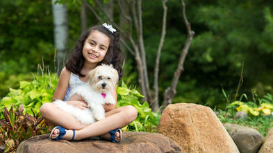 A 7-year-old child with shoulder-length curly dark hair cuddles a fluffy white puppy while sitting cross-legged on a large rock. The child is wearing a white lace tank top and shorts with blue sandals. In the background there are large green plants and trees.