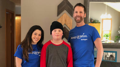 Two adults in royal blue Make-A-Wish t-shirts and jeans stand on either side of a child in a red and gray shirt and black beanie. The background is a living room with a gray couch and wooden wall art.