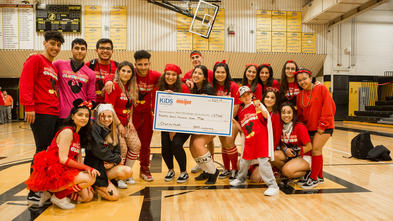 "17 high school students wear red headbands and shirts that read ""Sterling Heights Clubhouse"" as they pose in their school gymnasium with a child. The group holds an oversized check for $27,060 dollars made out to Make-A-Wish Michigan."