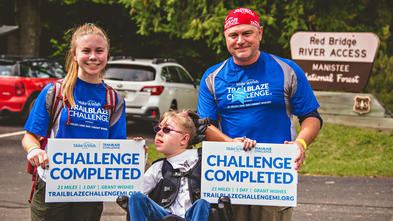 "A teenager with pink glasses and a messy blond ponytail sits in a wheelchair between their twin and father, who are both wearing royal blue shirts with the Trailblaze Challenge logo and holding signs that read ""Challenge Completed""."