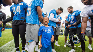 A child in a royal blue Make-A-Wish t-shirt and jean shorts stands amidst a crowd of football players wearing practice gear. The child is smiling at the camera, while the players are passing around and signing a football.