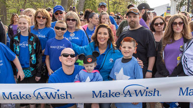 An adult with long brown hair is wearing a royal blue jacket and waiting at the center front of a large crowd of people with their arms around two children in Make-A-Wish t-shirts. In front, an adult wearing sunglasses is kneeling on one leg and holding a young child wearing Mickey Mouse ears on the other knee. A white banner patterned with royal blue Make-A-Wish logos is held in front of the crowd.