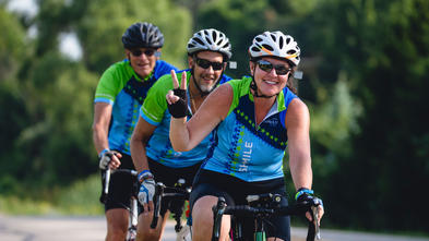 Three adult riders are shown pedaling their bikes in a line directly towards the camera. All three are wearing the 2019 WAM jersey—bright blue with lime green and navy accents and patterned with stars—bicycle helmets and sunglasses. The person in the front makes a peace sign with their fingers.