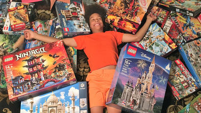 Noah with all of the LEGO sets from his wish
