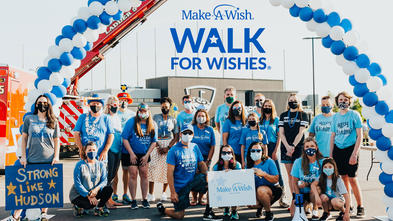 Group of people under a balloon arch and banner for Make-A-Wish Walk For Wishes event