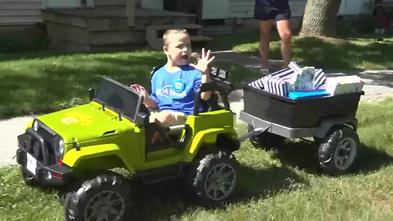 Bentley waves as he drives his new Power Wheels Jeep.