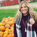 An adult with long straight blond hair, wearing a purple sweater with a white, purple and black plaid scarf and a white tassel necklace. The background is a pile of orange pumpkins with a green field and red barn.