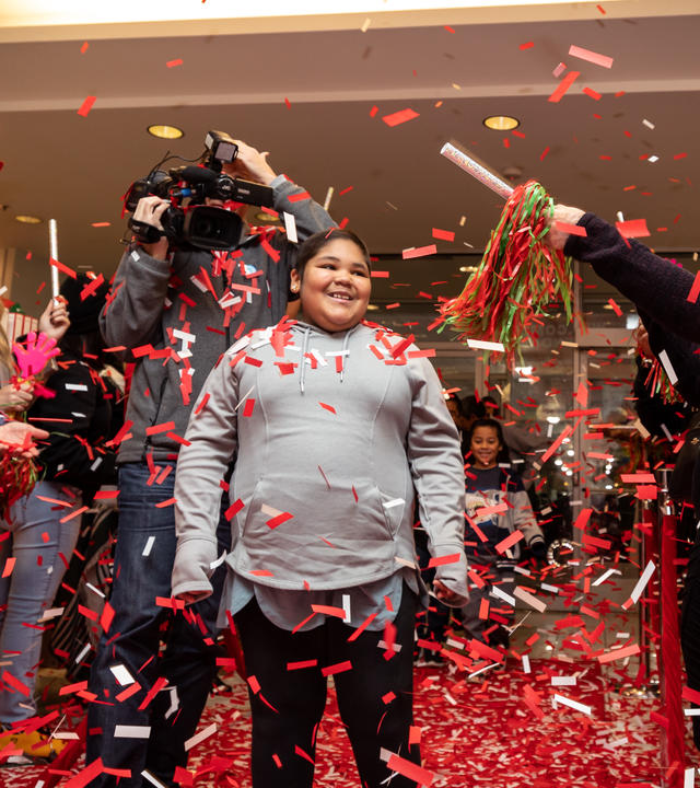 Glenda smiles as confetti falls at Macy's