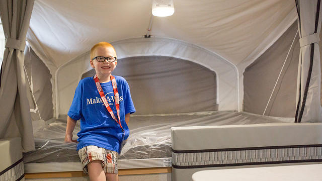 A child with short red hair and black glasses sits on the bed inside a camper. The child is wearing a royal blue Make-A-Wish t-shirt, tan plaid shorts, and a red lanyard with a large tag that says VIP.