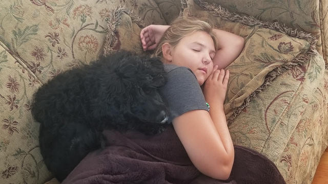 Diane snuggles with her puppy, Rosie, on the couch